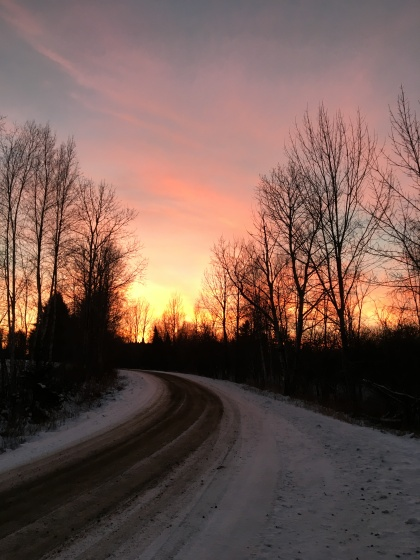 running on a snowy dirt road at sunset