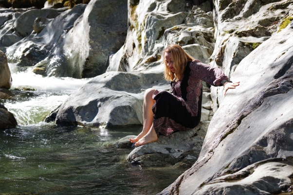 woman sitting next to the river