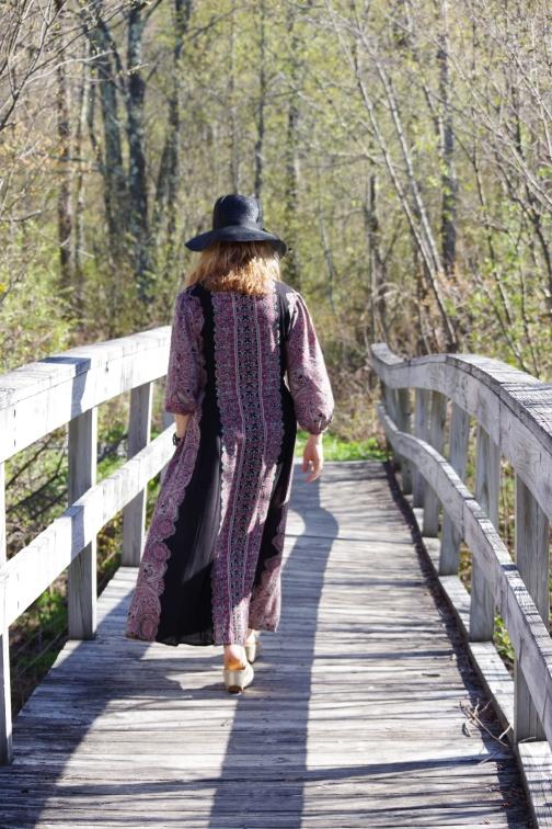 woman walking over a wooden bridge